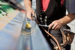 Närbild av en roofer som applicerar svetsningen in i avloppsrännan Arkivfoto