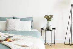Närbild av en säng med blek vis gräsplan- och vitlinne, kuddar och en filt i en solig sovruminre En rund svart metall sid fotografering för bildbyråer