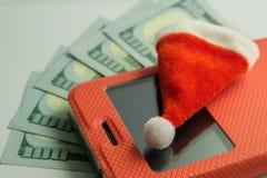 Närbild av en Santa Claus souvenirhatt som ligger på en smartphone i ett rött fall mot bakgrunden av femhundra US dollar _ royaltyfri bild