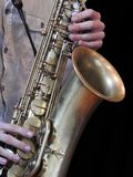Närbild av en saxofonist som spelar hans instrument, en saxofon royaltyfria bilder