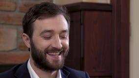 Närbild av en skäggig manskådespelare i en dräkt Uppvisning av ett förälskelseleende stock video