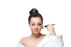 Närbild av en skönhetkvinna som gör hennes makeup arkivbild