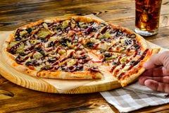 Närbild av en skiva av pizza i hand arkivbilder