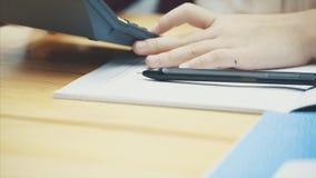 Närbild av en skolflickas hand som skriver läxa Det är nödvändigt att räkna på en dator stock video