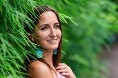 Närbild av en stående av en flicka med ett leende nära ett naturligt staket av gräs fotografering för bildbyråer
