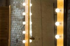 Närbild av en stor spegel i ett rum med en tegelstenvägg royaltyfri bild