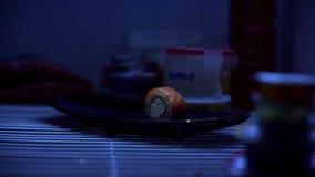 Närbild av en sushirulle på plattan Ensam sushirulle med laxen och ost är på den svarta plattan, som tar handen in arkivfilmer