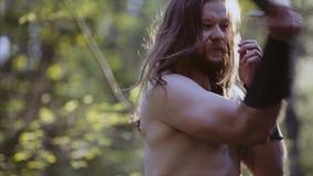 Närbild av en tuff grabb med långt hår och en kniv i hans händer Han slår på en imaginär fiende arkivfilmer