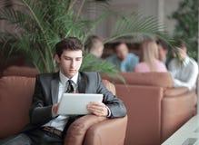Närbild av en ung affärsman som använder ett digitalt minnestavlasammanträde i lobbyen av banken royaltyfri foto