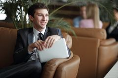 Närbild av en ung affärsman som använder ett digitalt minnestavlasammanträde i lobbyen av banken arkivfoton