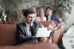 Närbild av en ung affärsman som använder ett digitalt minnestavlasammanträde i lobbyen av banken arkivbild