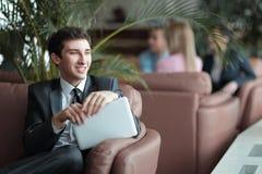 Närbild av en ung affärsman som använder ett digitalt minnestavlasammanträde i lobbyen av banken fotografering för bildbyråer