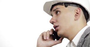 Närbild av en ung byggnadsarbetare i en vit hjälm som talar på en mobiltelefon lager videofilmer
