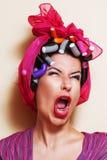Närbild av en ung kvinna med papiljotter som gör en grimas Arkivfoton