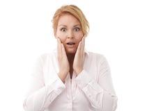 Närbild av en ung kvinna som ser förvånad mot vit backgr Fotografering för Bildbyråer