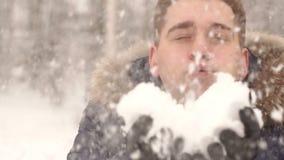 Närbild av en ung man som blåser på snön arkivfilmer