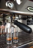 Närbild av espresso som häller från kaffemaskinen in i de två högväxta exponeringsglasen Arkivbilder
