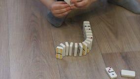 Närbild av ett barn som hemma spelar med dominobrickor på golvet arkivfilmer
