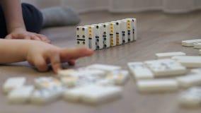 Närbild av ett barn som hemma spelar med dominobrickor på golvet lager videofilmer
