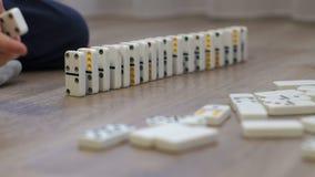 Närbild av ett barn som hemma spelar med dominobrickor på golvet stock video