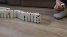 N?rbild av ett barn som hemma spelar med dominobrickor p? golvet lager videofilmer