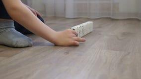 N?rbild av ett barn som hemma spelar med dominobrickor p? golvet arkivfilmer
