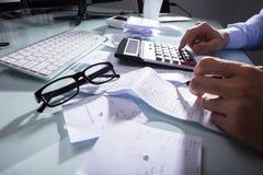 Närbild av ett beräknande kvitto för Businessperson` s royaltyfri foto