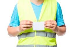 Närbild av ett emblem i händerna av en arbetare i en gul waistco royaltyfria bilder