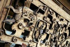 Närbild av ett motiv av ett drakehuvud på ett trämöblemang arkivfoto