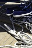 Närbild av ett rep med ett knutit slut som binds runt om en dubb på en träpir och skor med ankaren royaltyfri bild
