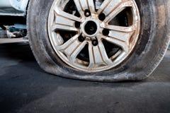 Närbild av ett skadat plant gummihjul av en bil arkivbild
