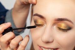 Närbild av ettstil ögonsmink: guld-, bruna och gröna uttalade ögonskuggor, sminkkonstnären rymmer en borste i hans fotografering för bildbyråer