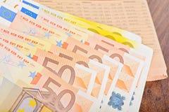 Närbild av eurosedlar med tidningen Arkivfoton