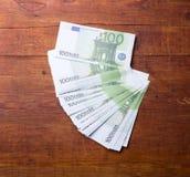 Närbild av 100 eurosedlar på trä Arkivfoto