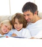 Närbild av fadern och hans barnavläsningsbok Arkivbilder