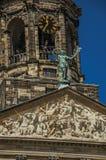 Närbild av fasaden med skulpturer och kupolen med den guld- klockan i Royal Palace av Amsterdam Fotografering för Bildbyråer