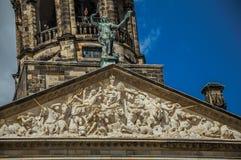 Närbild av fasaden med skulpturer och kupolen med den guld- klockan i Royal Palace av Amsterdam Royaltyfria Bilder