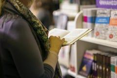 Närbild av flickan med boken i händer, bokhandel Utbildning skola, studie, läs- fiktionbegrepp Verklig plats i Royaltyfri Bild