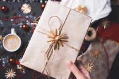 Närbild av flickan som rymmer en hemlagad gåvaask av Kraft papper på bakgrunden av jultabellen royaltyfri bild