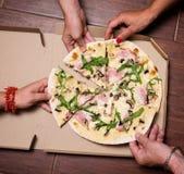 Närbild av folkhänder som tar skivor av pizza Grupp av vänner som tillsammans delar pizza Äta mat Snabbmat kamratskap, arkivbild