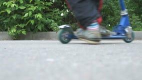 Närbild av fot av pojken i gymnastikskor på sparkcykeln lager videofilmer