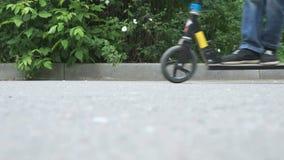 Närbild av fot av pojken i gymnastikskor på sparkcykeln stock video
