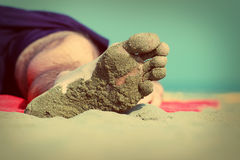 Närbild av foten av en sova man som ligger på stranden Arkivbild