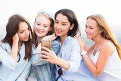 Närbild av fyra härliga unga kvinnliga studenter som gör selfies och att le arkivbilder