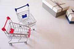 Närbild av gåvaaskar och shoppingvagnar på det vita skrivbordet arkivbild