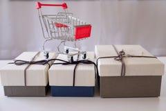 Närbild av gåvaaskar och shoppingvagnen på det vita skrivbordet arkivfoto
