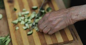Närbild av gamla rynkiga händer som gör en ny sallad av grönsaker lager videofilmer