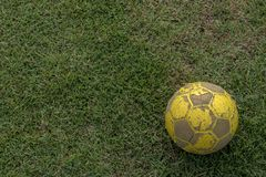 Närbild av gammal fotboll som ligger på gräs royaltyfria bilder