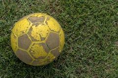 Närbild av gammal fotboll som ligger på gräs fotografering för bildbyråer