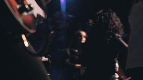 Närbild av gitarristen som spelar på etappen med övergången av kameran till de fantastiska flickaviolinisterna arkivfilmer